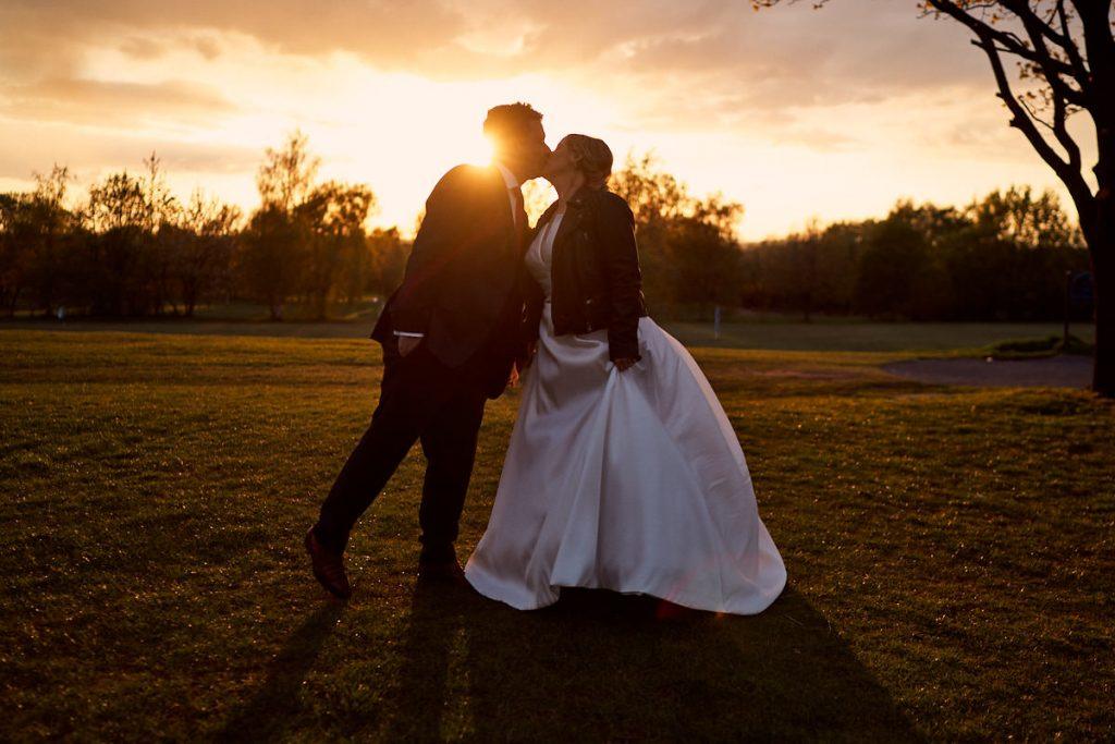 bride and groom kissing at sun set
