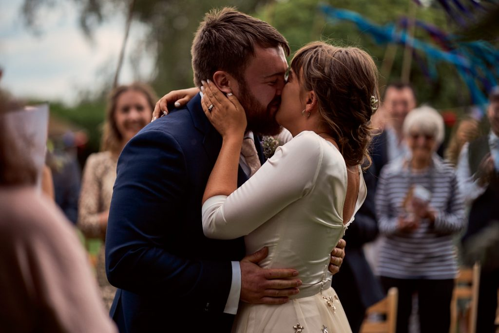 bride and grooms first kiss during their garden wedding in taunton