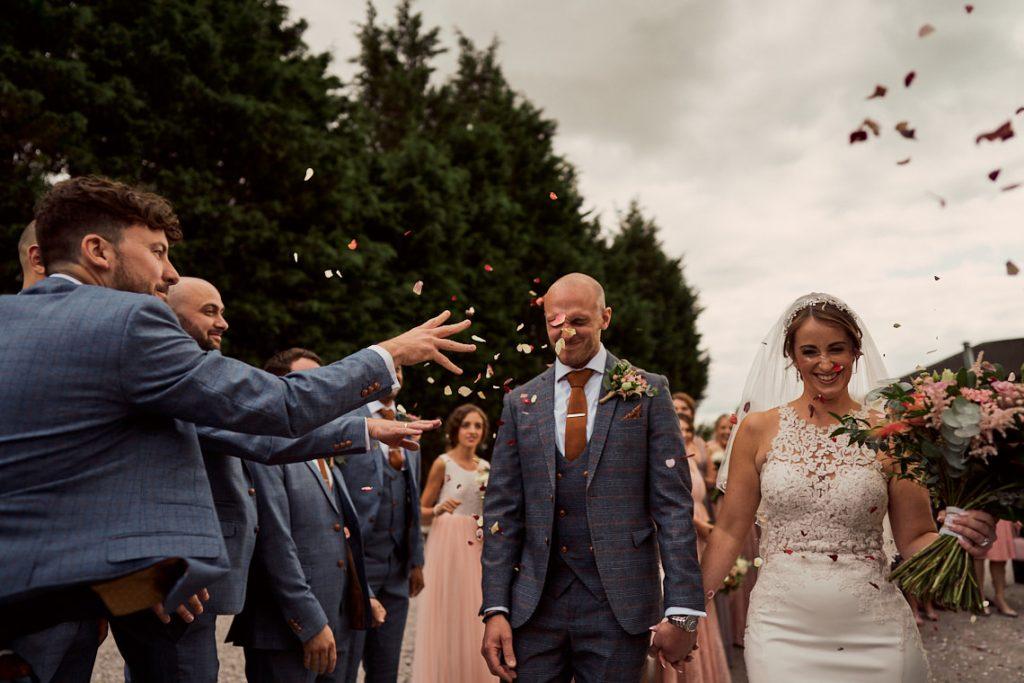 bride and groom having confetti thrown at them in Alcumlow wedding barns courtyard