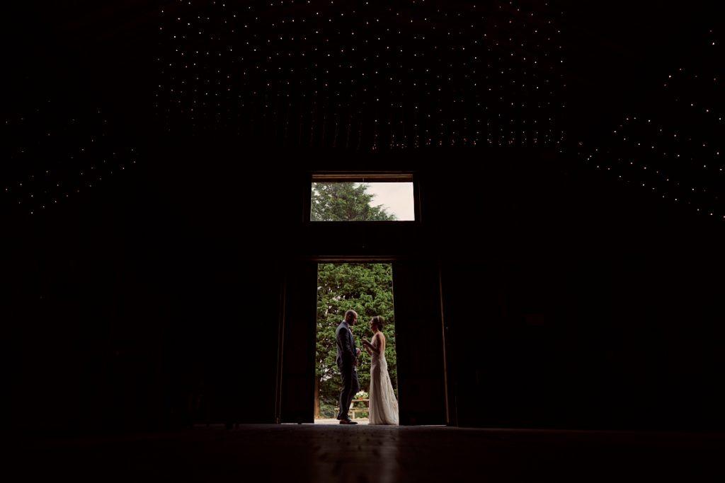 bride and groom standing in the barn doors of Alcumlow low wedding barn