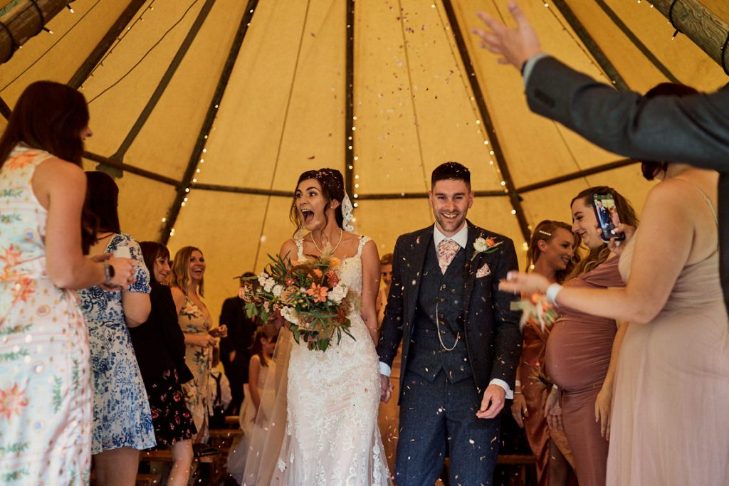 bride and groom leaving the upstream ceremony tipi at Gisburne Park