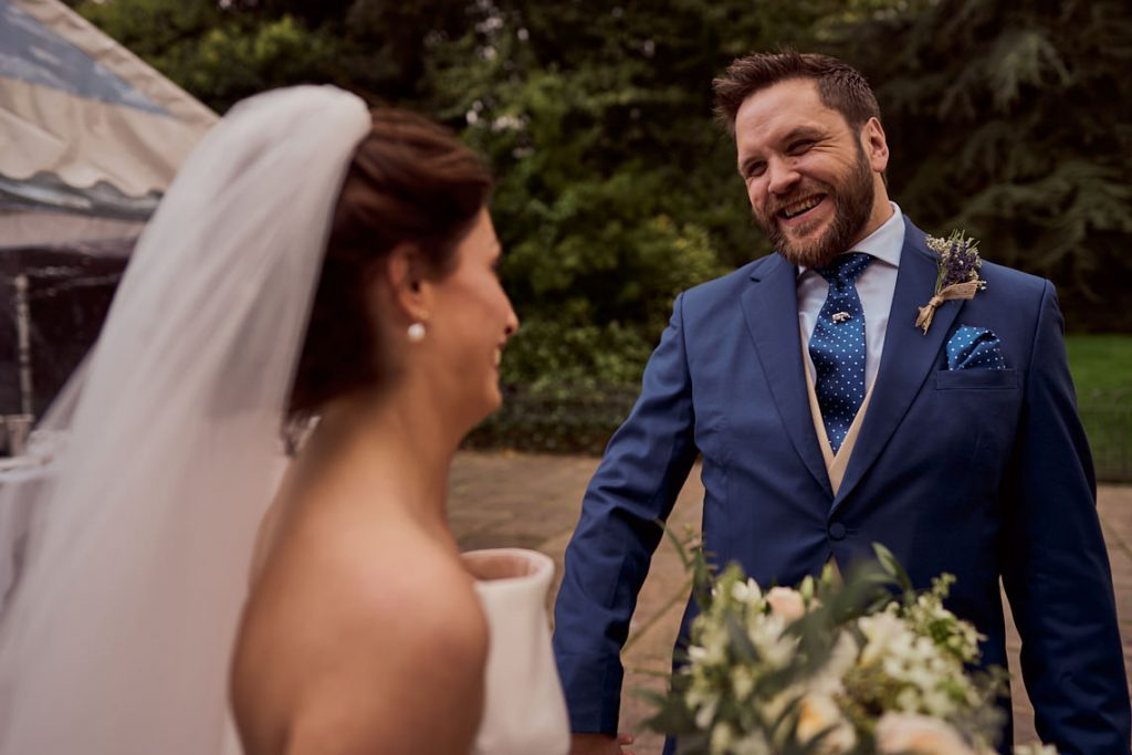 happy groom smiling at his new wife