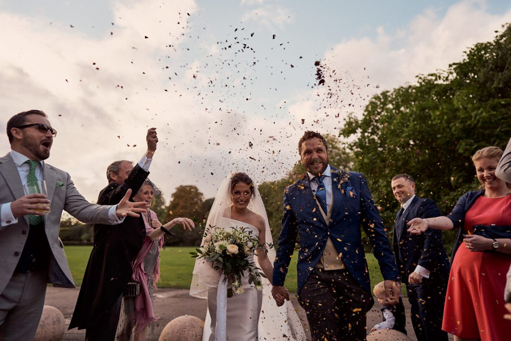 wedding guest throwing confetti at newly wed couple