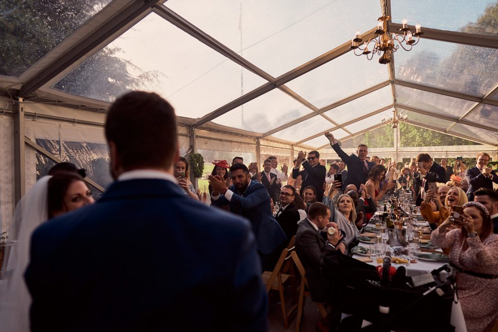 wedding guests cheering for the newly married couple