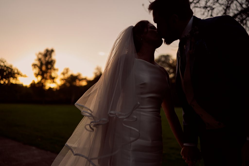 bride and groom kissing at sunset in Battersea park