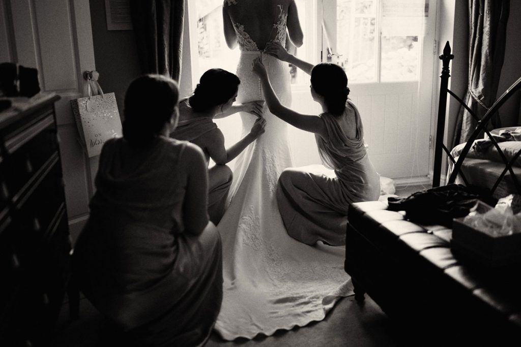 Bridesmaids adjusting the Bride's wedding dress