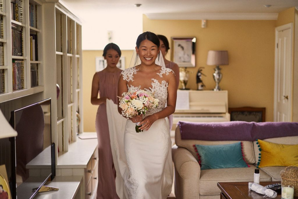 Bride smiling as she goes to meet her dad