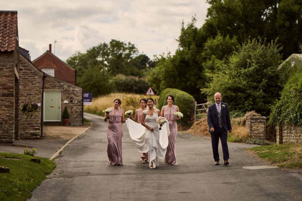 wedding party walking through Yorkshire village on their way to the church