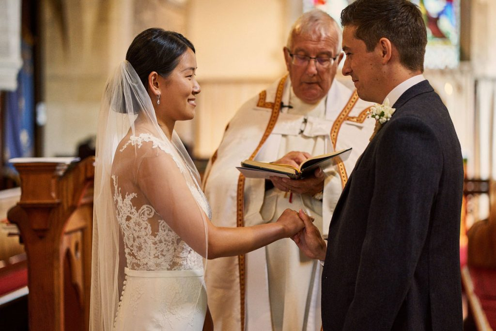 Bride & Groom holding hands during village church wedding ceremony