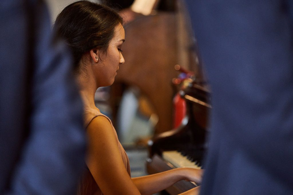 Bridesmaid playing piano during wedding service