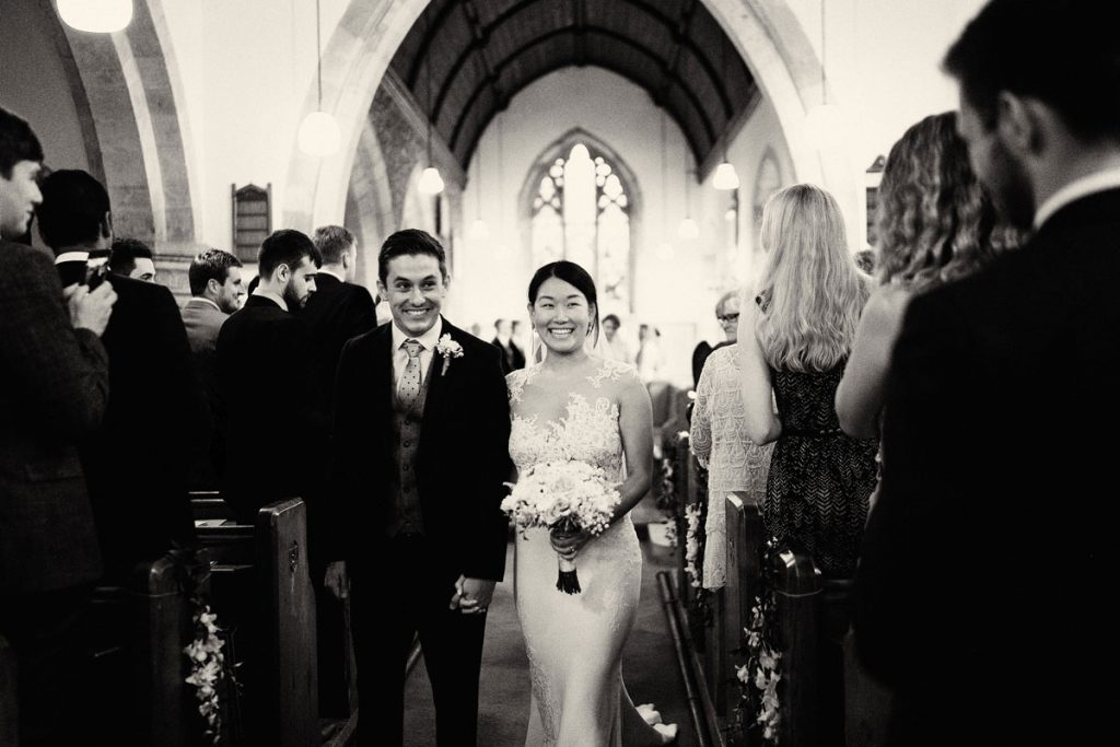 Bride & Groom smiling as they leave the church just after getting married