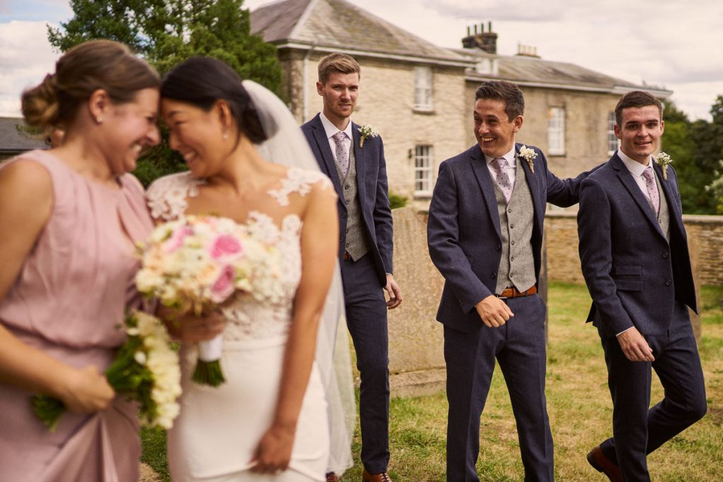 bride & Bridesmaid smiling with Best Men & Groom celebrating in the background