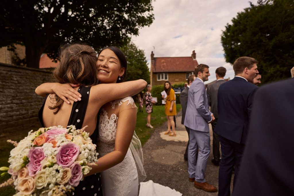 wedding guest giving Bride big hugs
