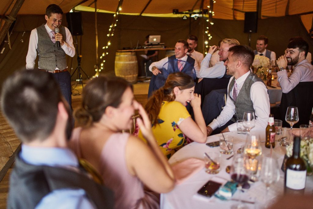 wedding guest laughing hard at grooms speech
