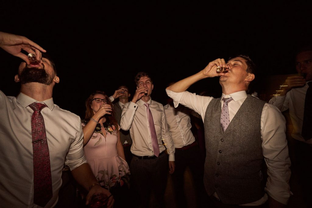 Groom doing shots at wedding