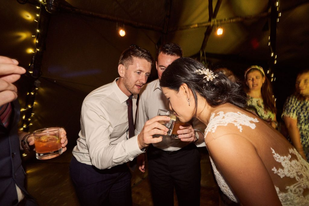 Bride drinking from wedding guest glass