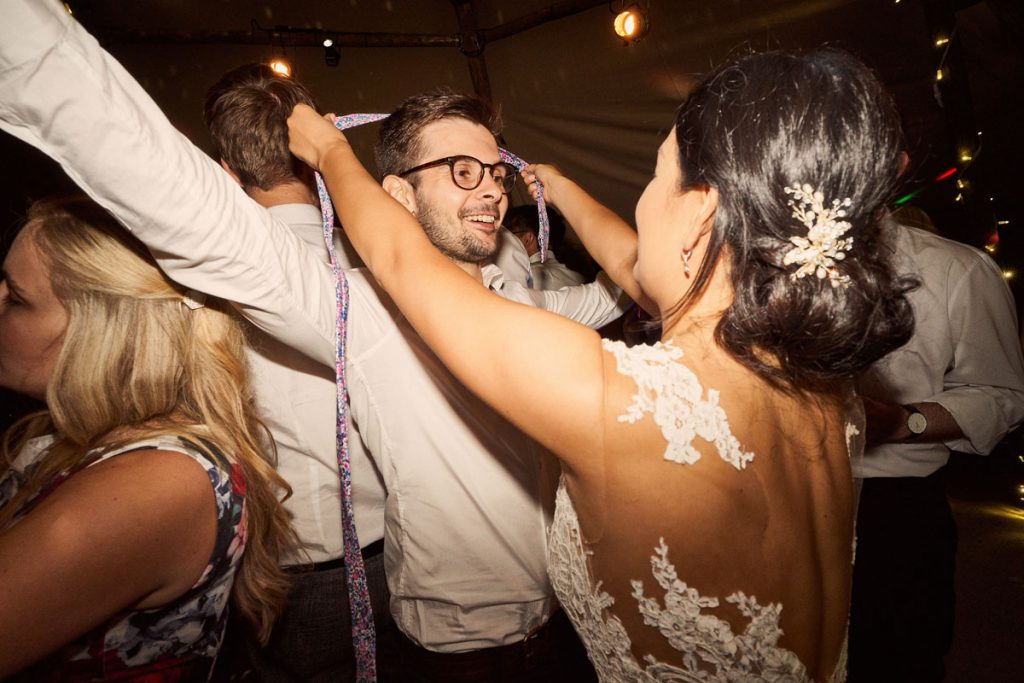 Bride tying a tie around wedding guests head