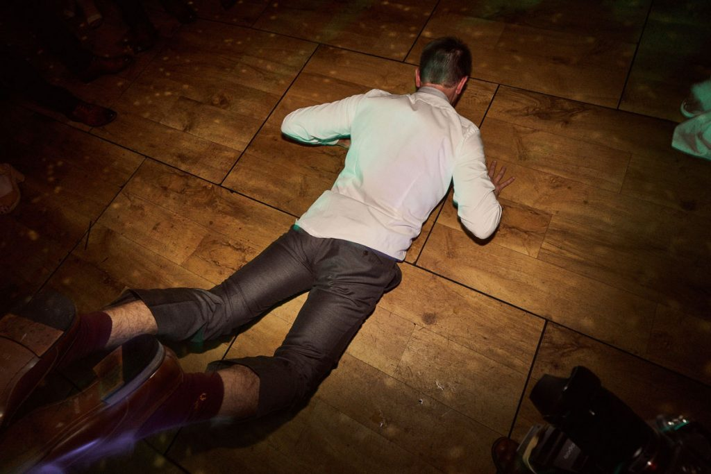 wedding guest doing the worm on dance floor