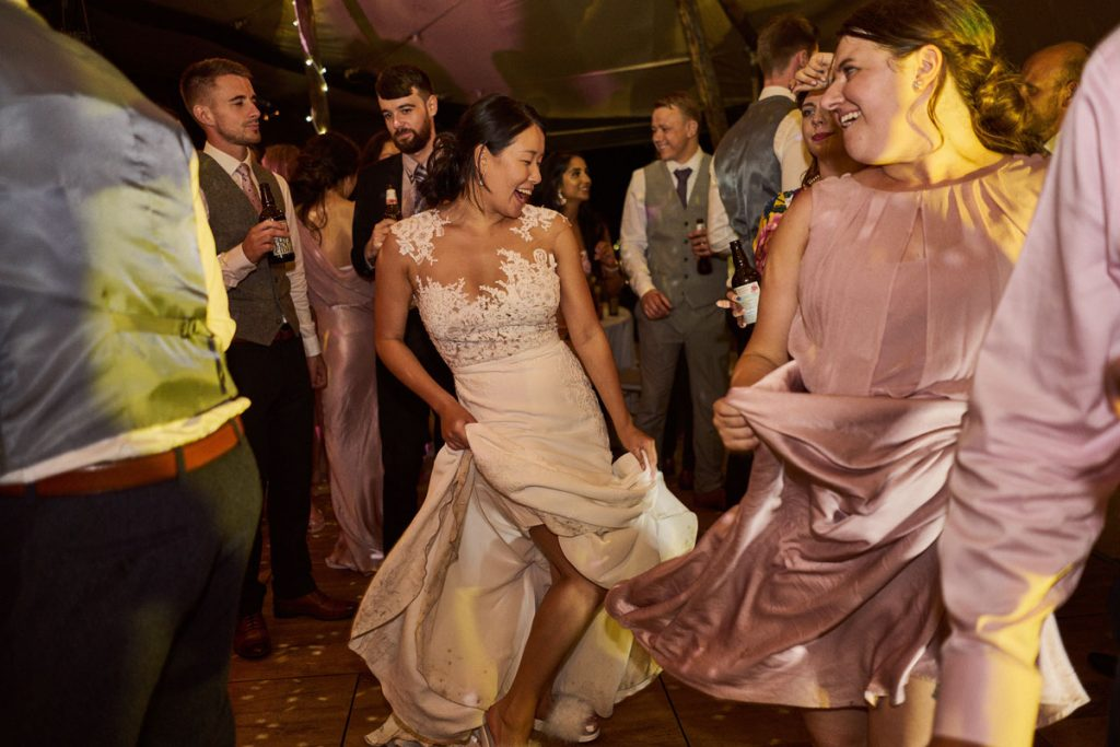 Bride swishing her wedding dress as she dances