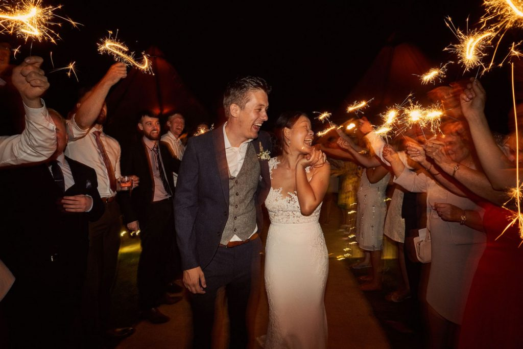 Bride & Groom leaving the tipi while guests wave sparklers