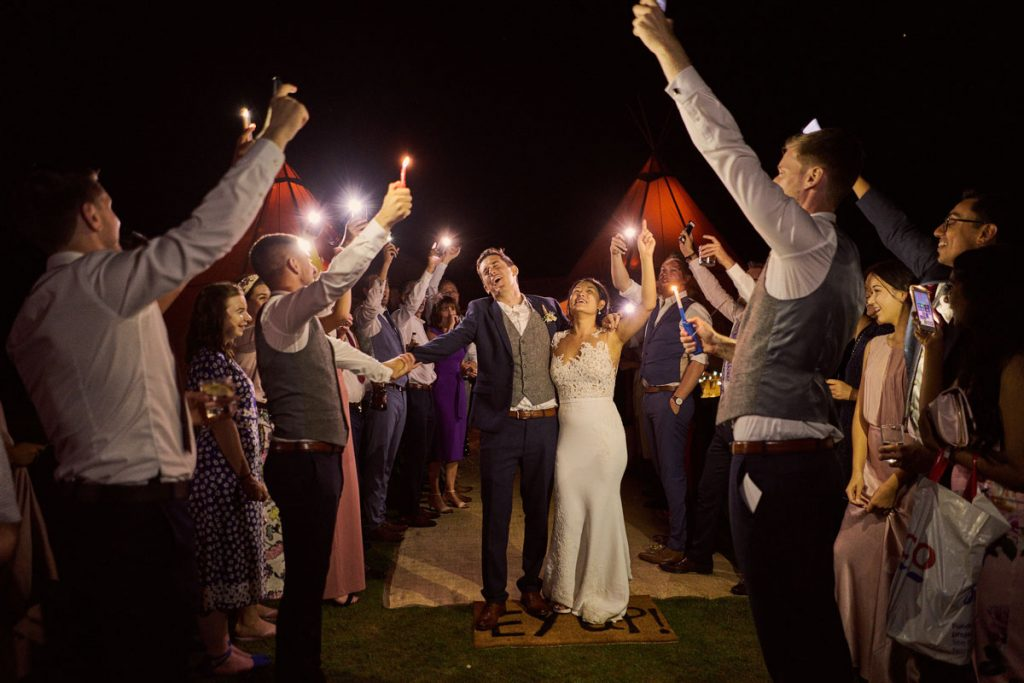 Bride & Groom leaving tipi, arm in arm with guests waving sparklers