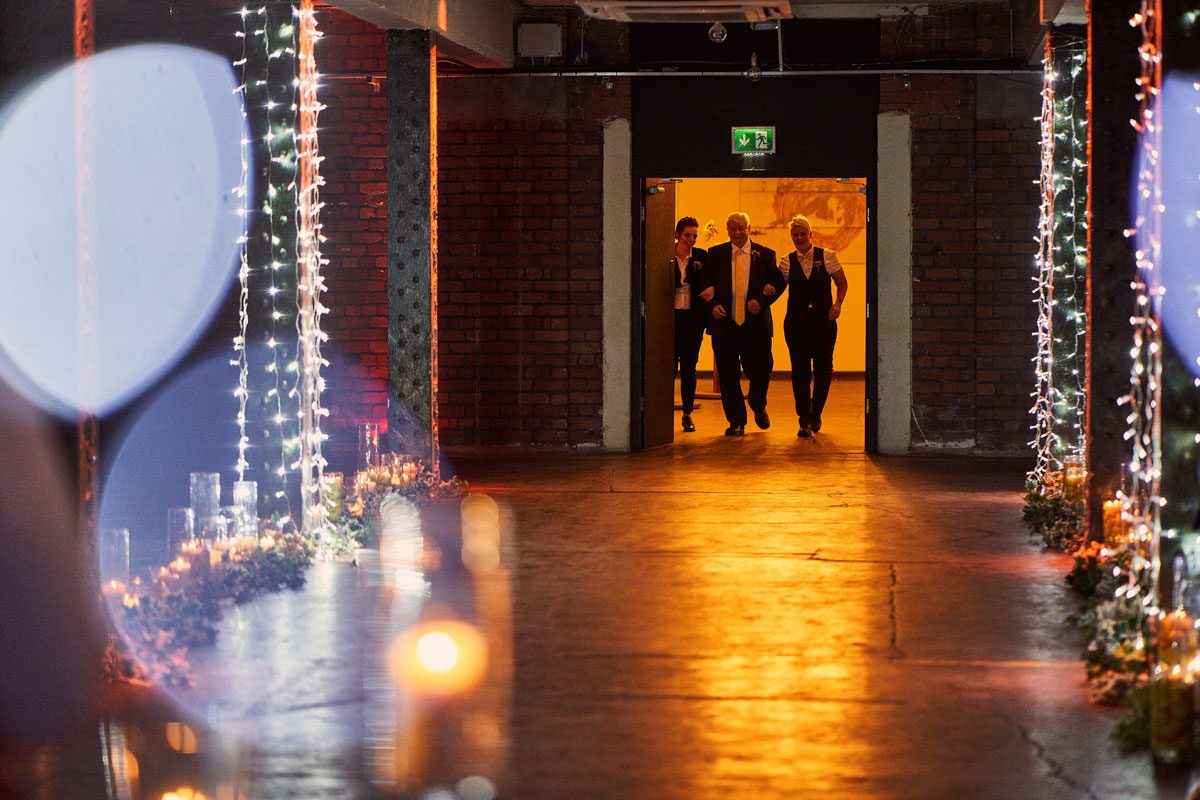 two brides walking down the aisle at Victoria Warehouse with the Bride father