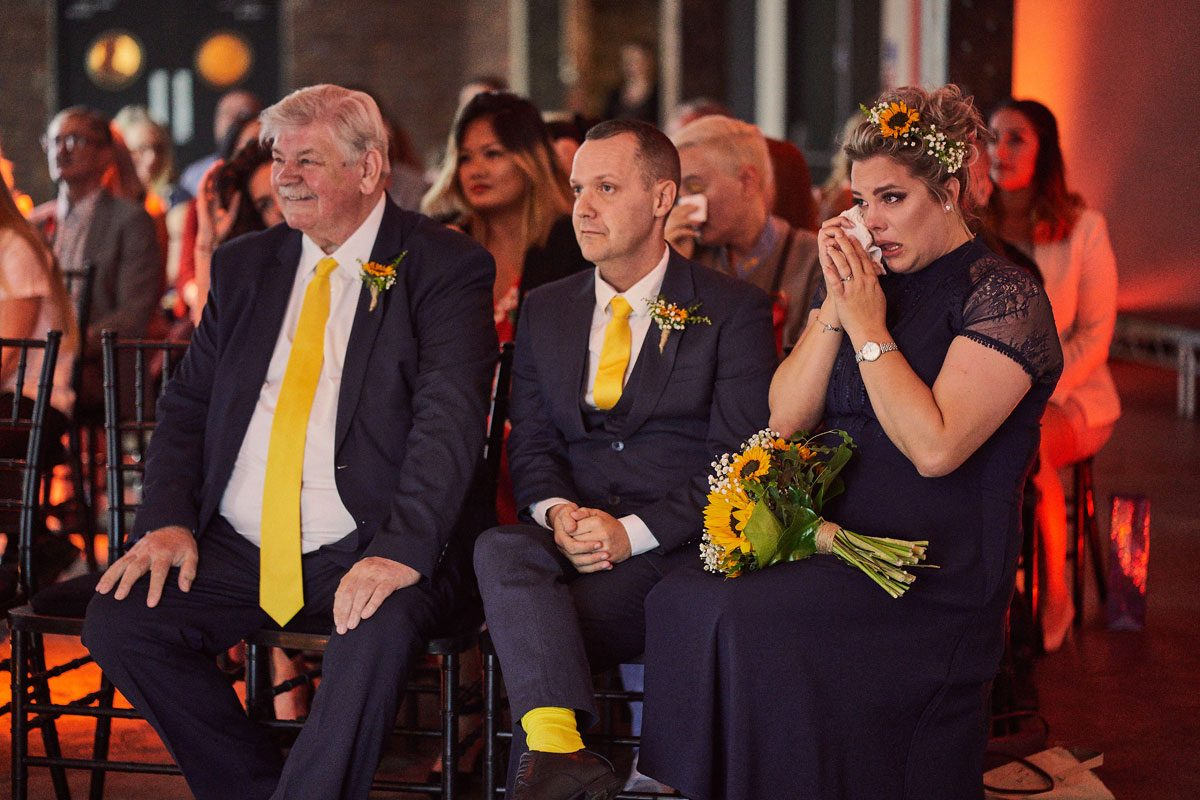 Bridesmaids crying during Victoria Warehouse wedding ceremony