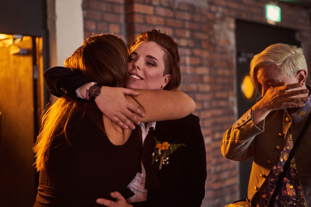brides hugging wedding guest at Victoria Warehouse