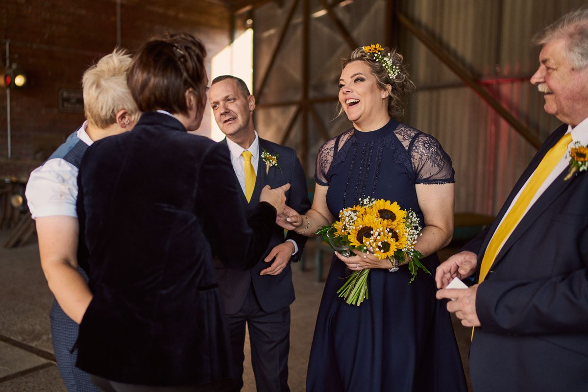Bridesmaids smiling with her sunflower bouquet