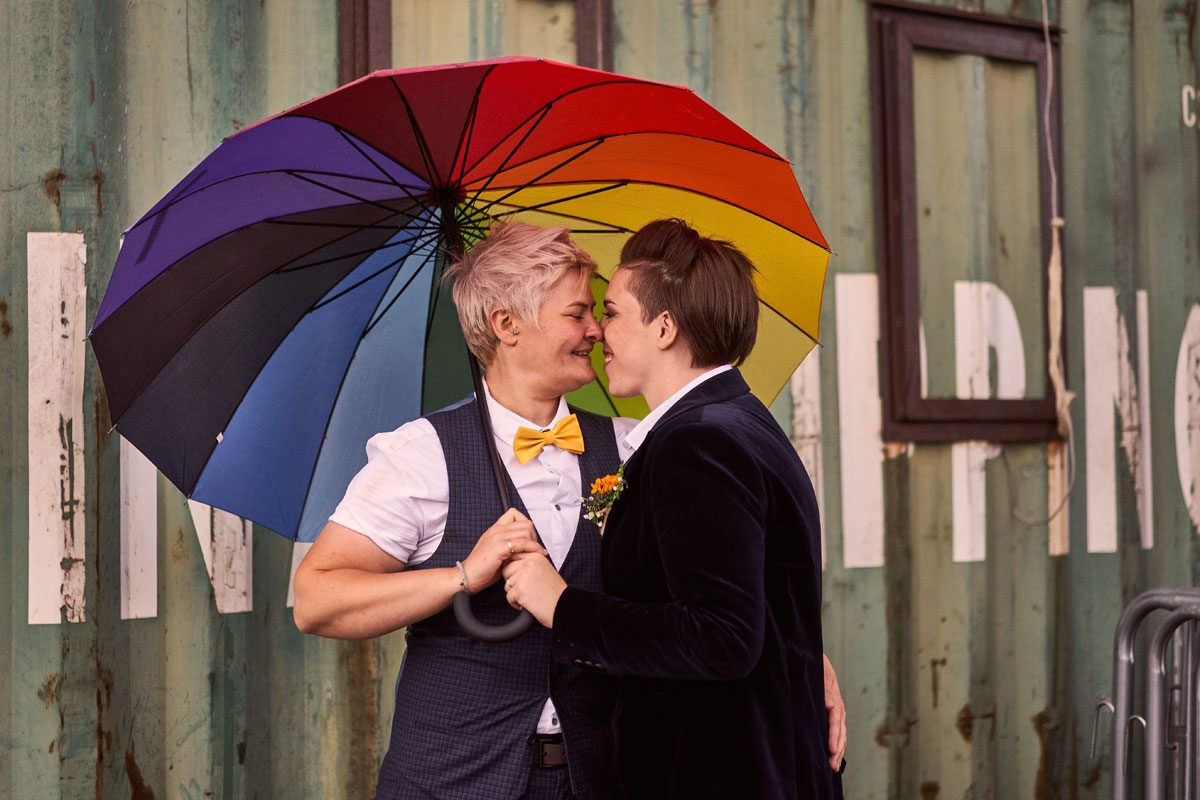 two brides touching noses under rainbow umbrella