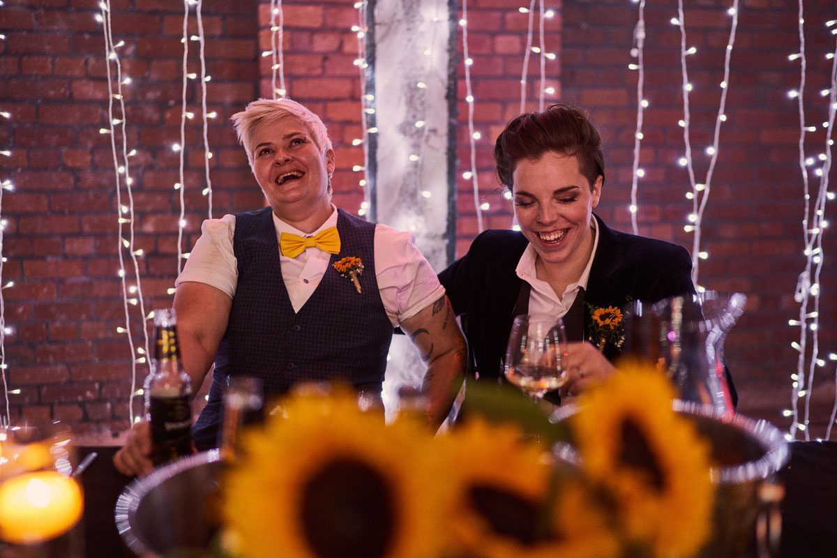 two brides laughing during speeches
