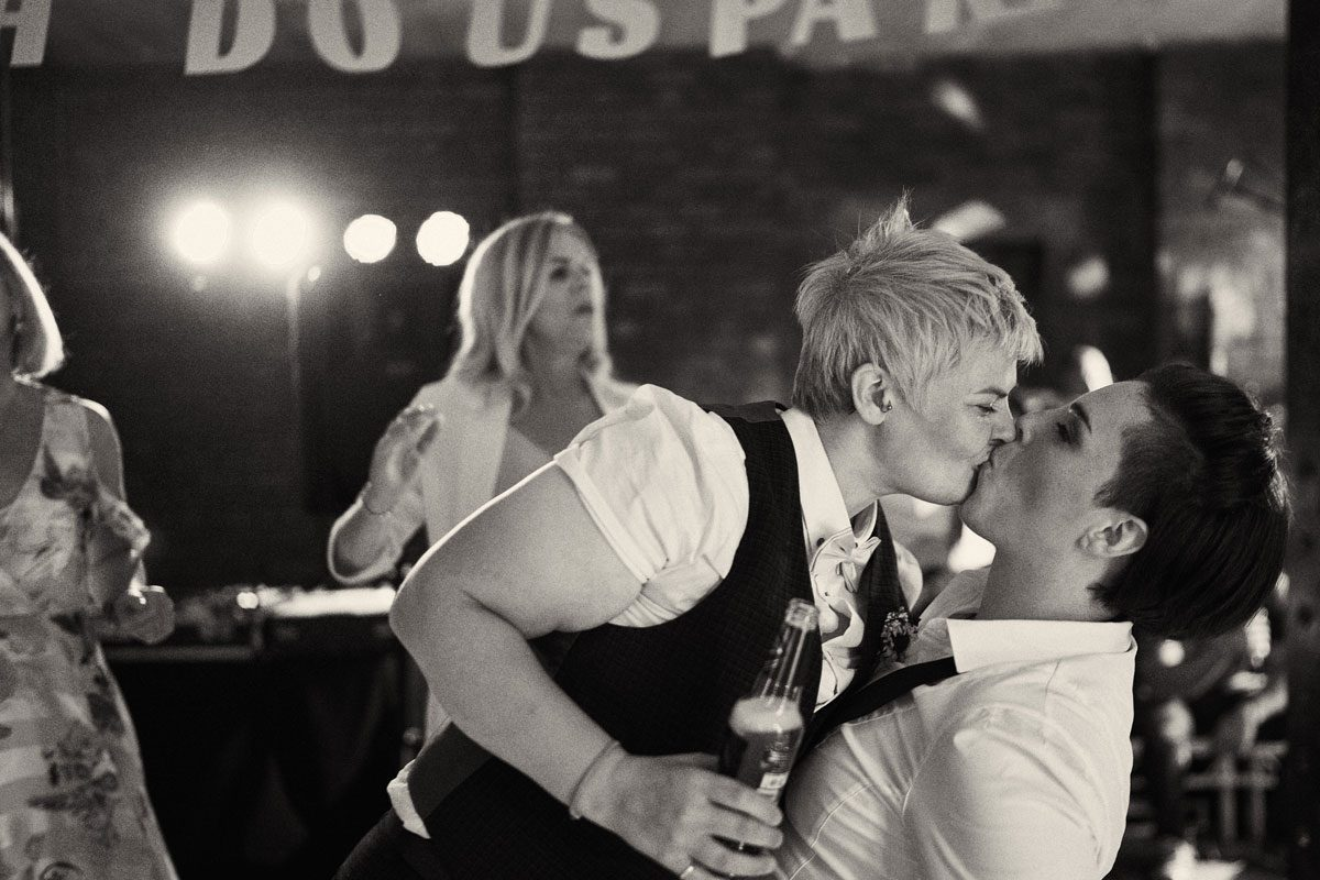 brides kissing each other on the dance floor