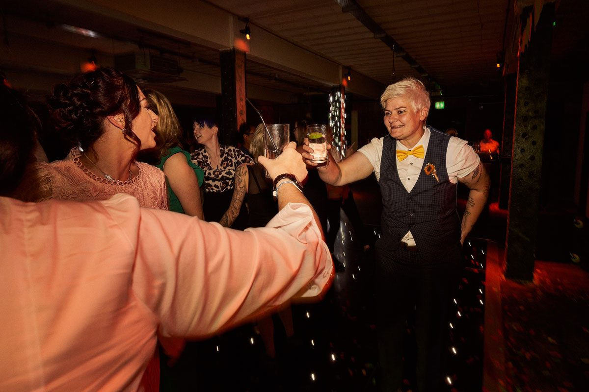 Bride clinking glasses on Victoria Warehouse dance floor