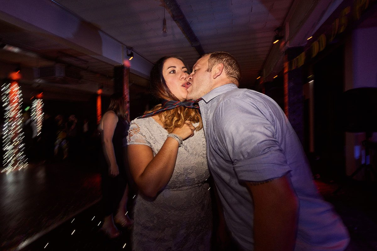 drunk wedding guest kissing partner