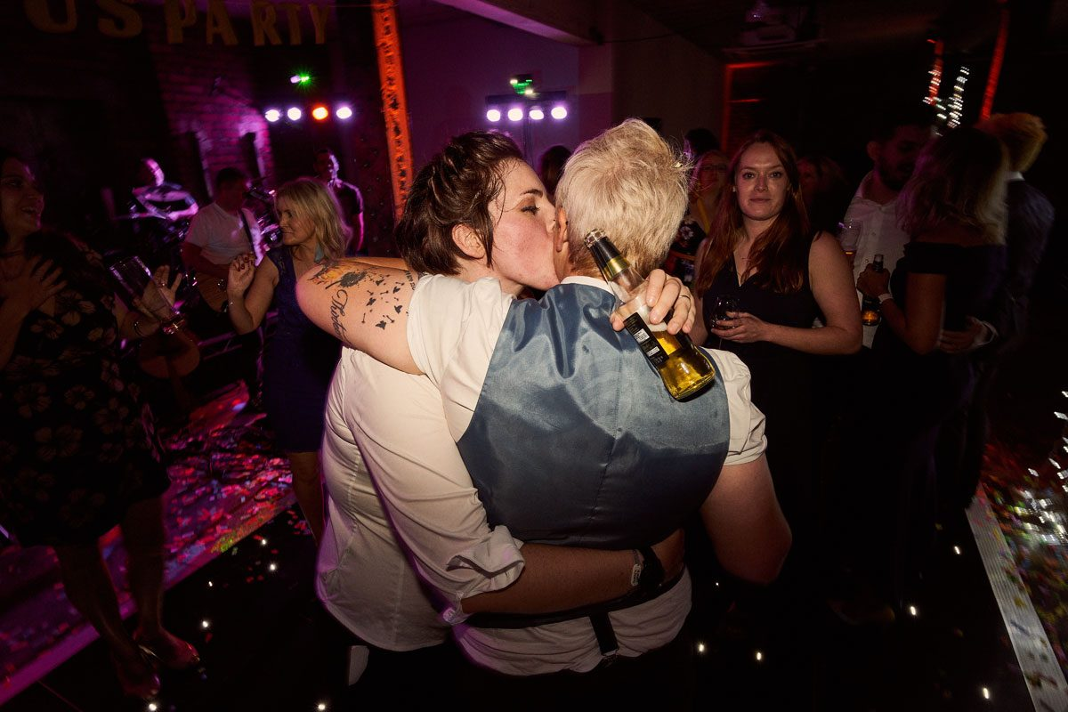 two brides hugging and dancing at the end of the night