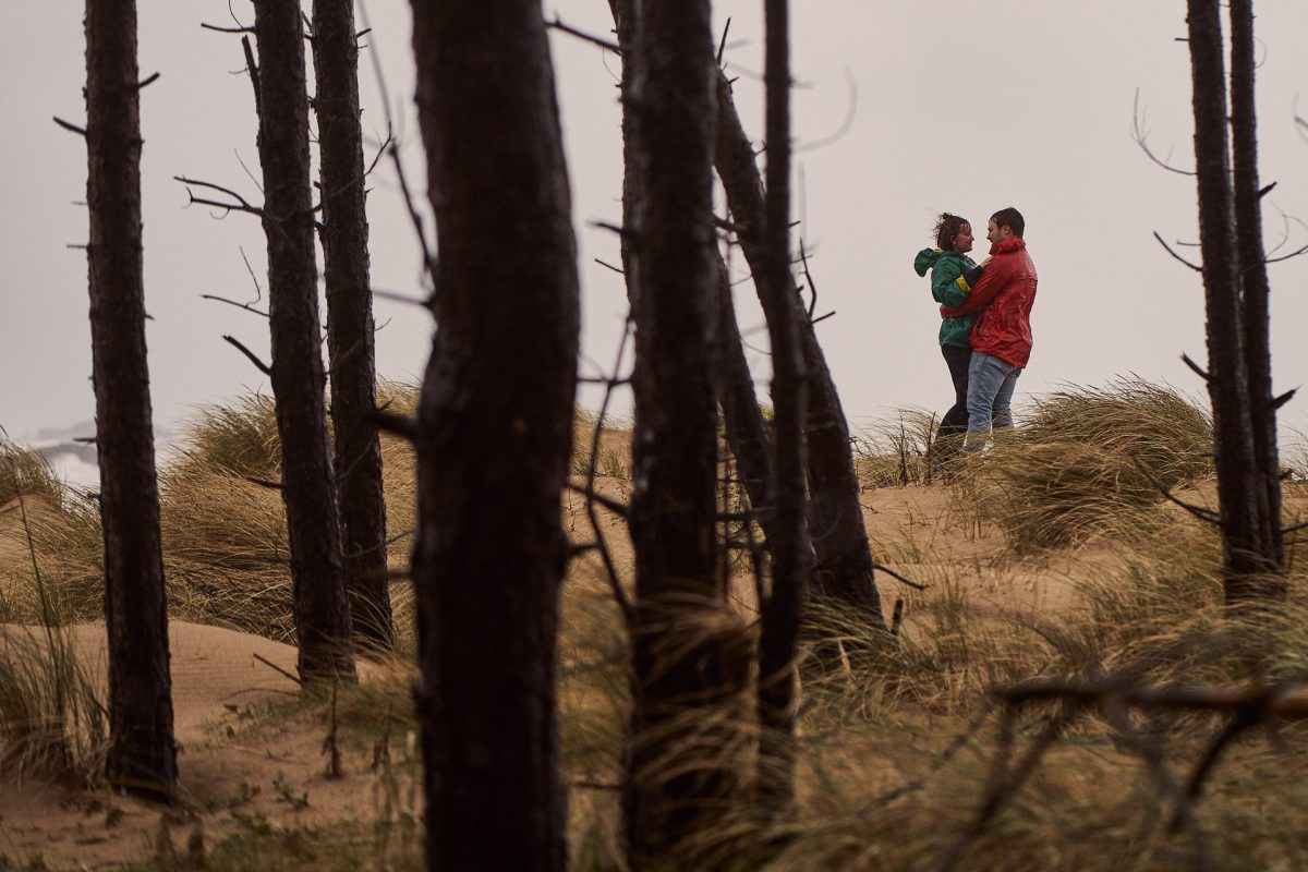 couple embrace each other at the top of the sand dunes at Llanddwyn Island
