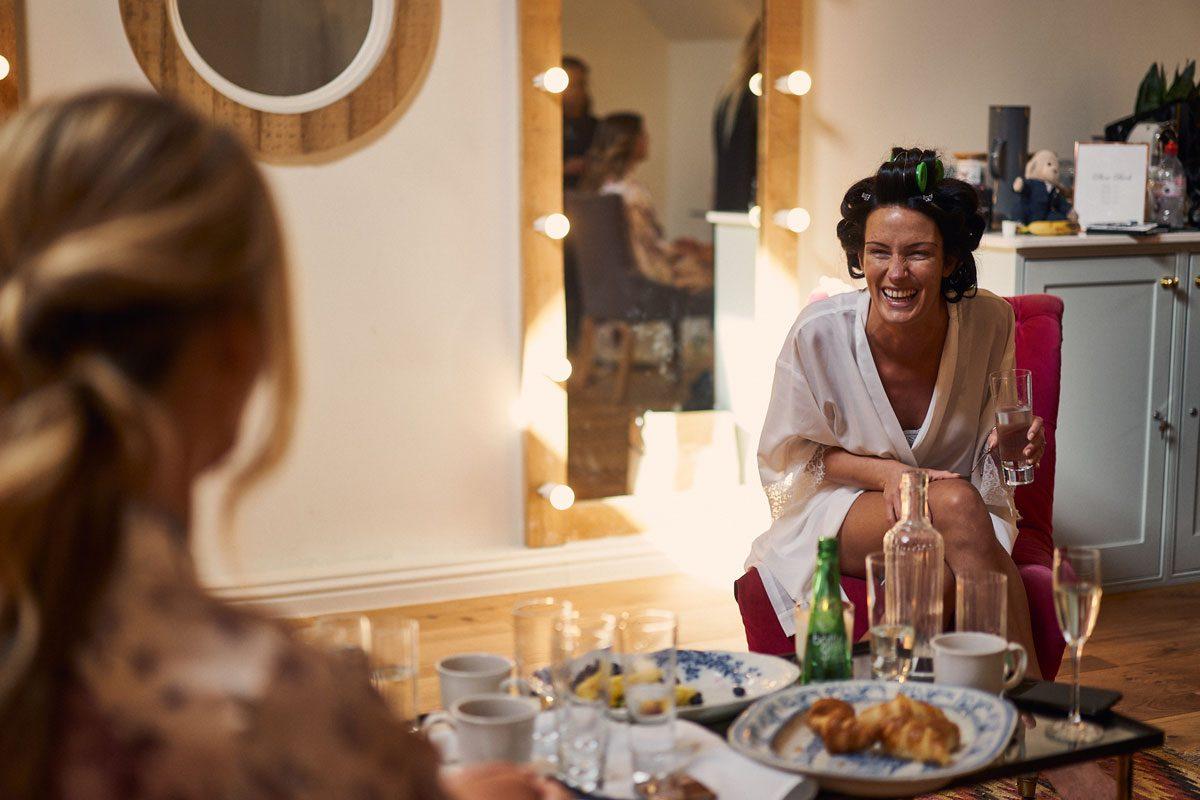Bride laughing while having breakfast at Millbridge Court