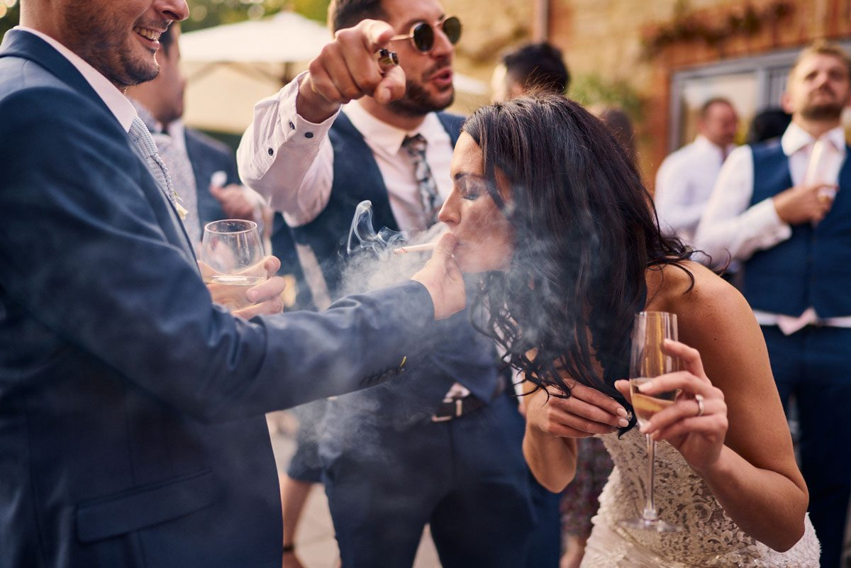 Bride taking a drag of a wedding guest cigarette