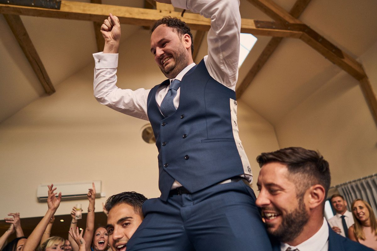 Best Men lifting Groom up onto their shoulders