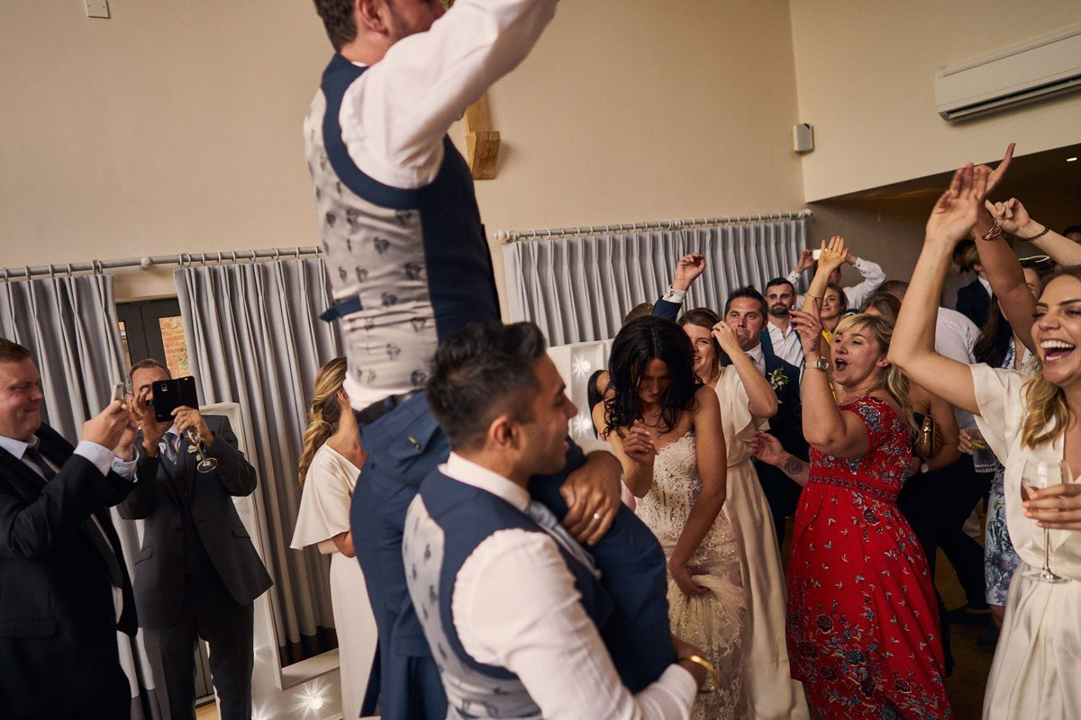 Best Men lift the Groom up onto their shoulder while everyone dances around them.