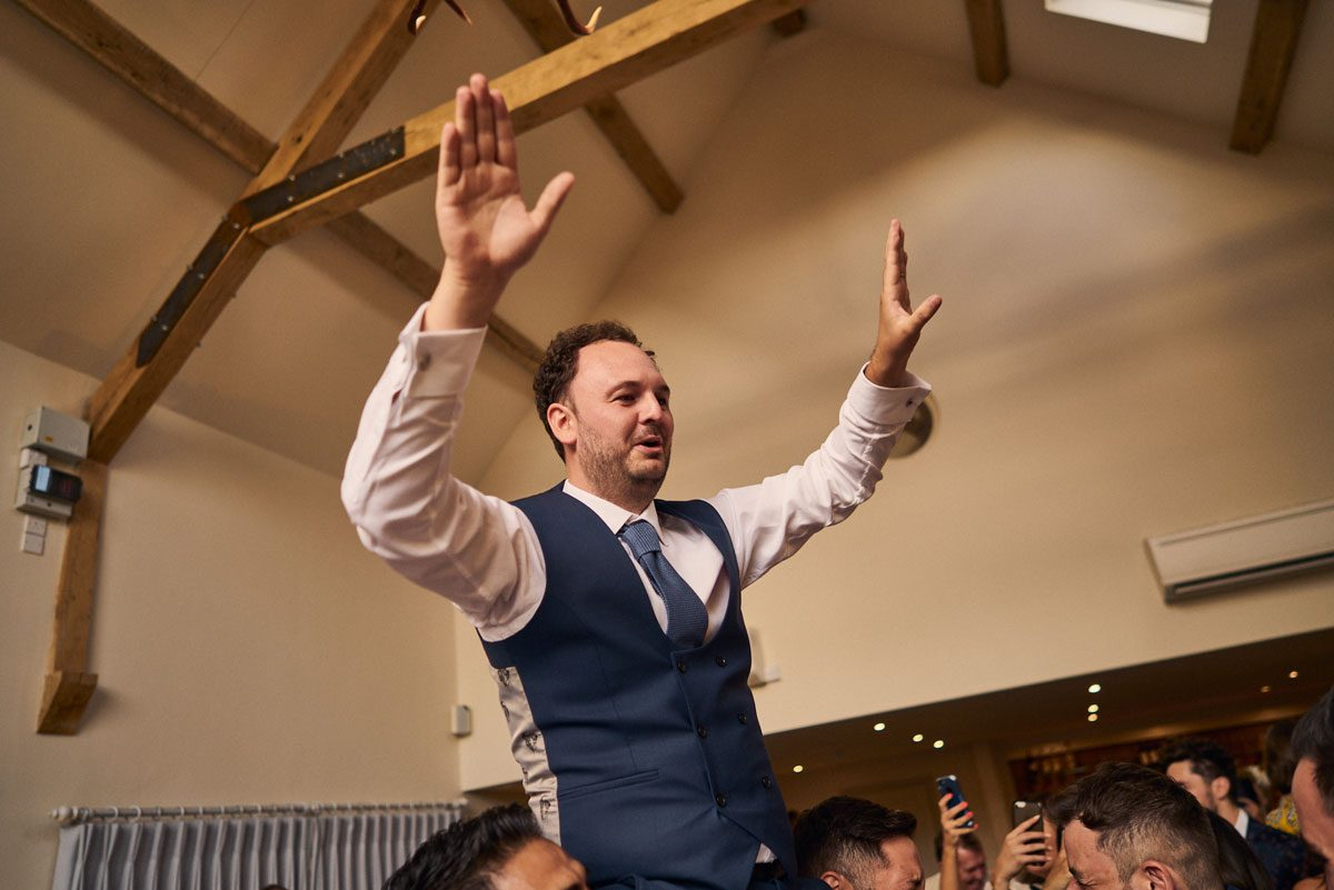 Groom waving his hands while on Best Man should
