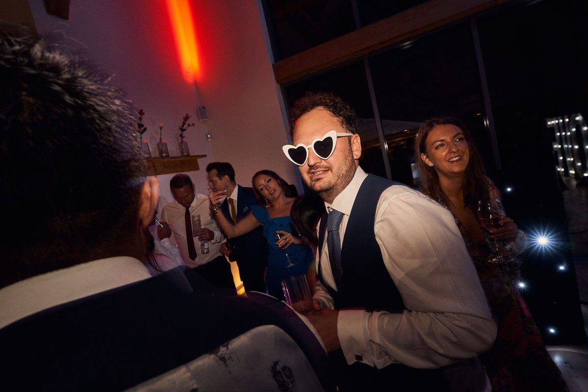 Groom with sunglasses on, on the dancefloor