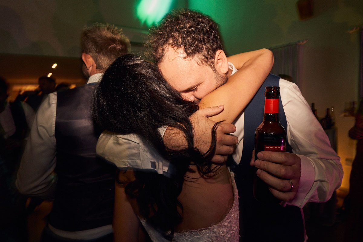 Groom hugging Bride with a beer in his hand