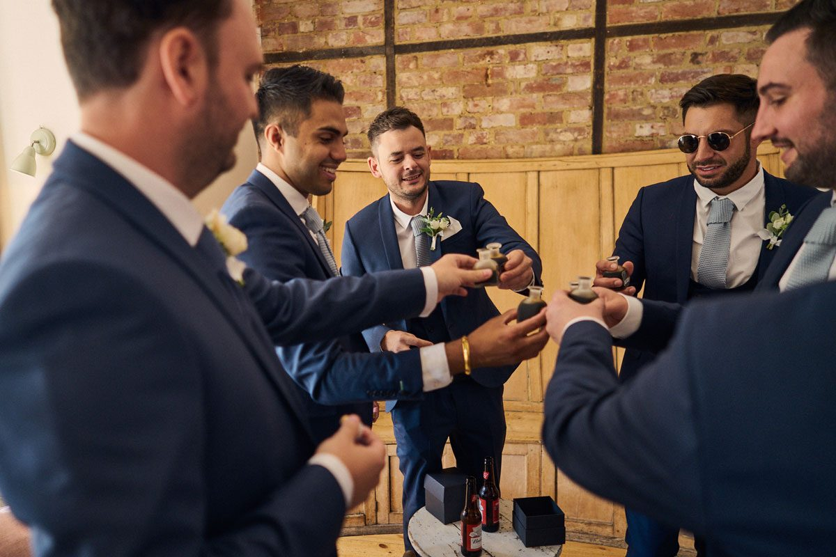 groomsmen having a shot before the wedding