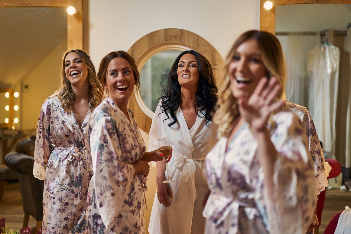 Bridesmaids all laughing and joking with bride