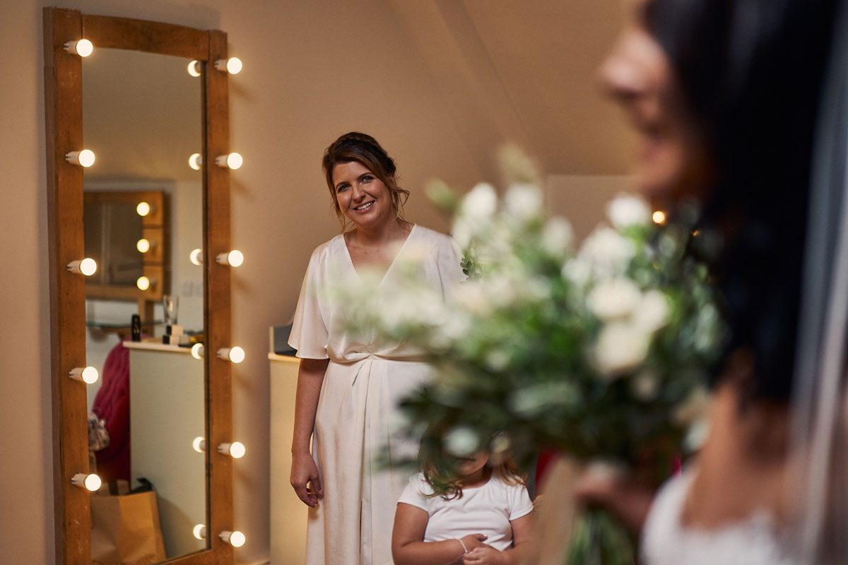 Bridesmaid smiling at Bride