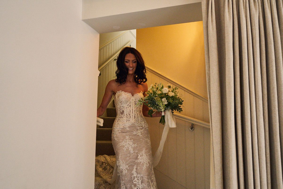 bride smiling as she comes down the stairs to see her father