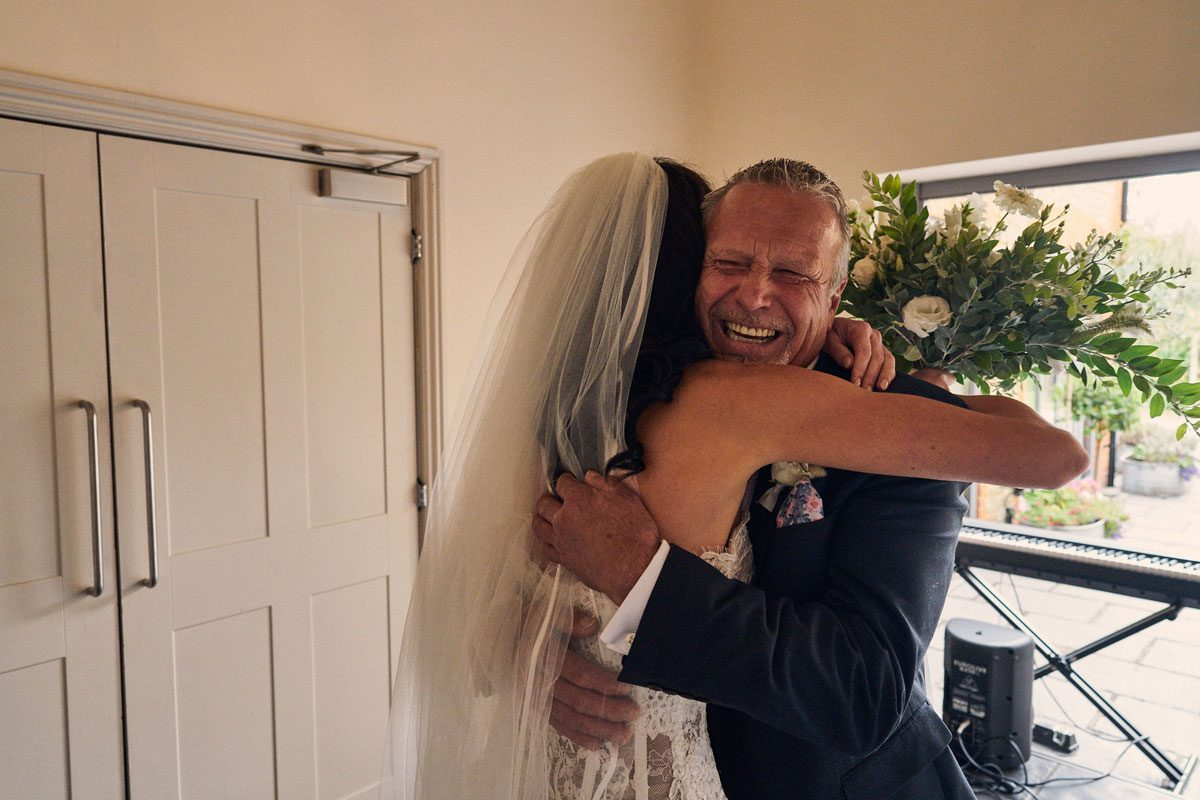 bride hugging her dad with dad beaming with pride