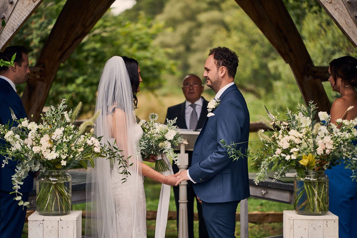 Bride & Groom holding hands while saying their wedding vows