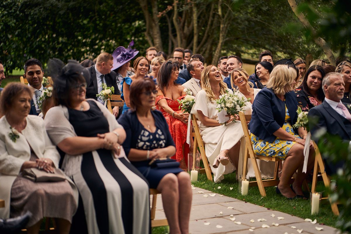 wedding guests laughing outside at Millbridge Court